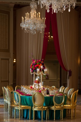 turquoise linen pink florals and napkins gold chairs multi colored arrangement