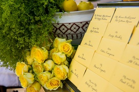 Wedding reception table with yellow place cards and roses