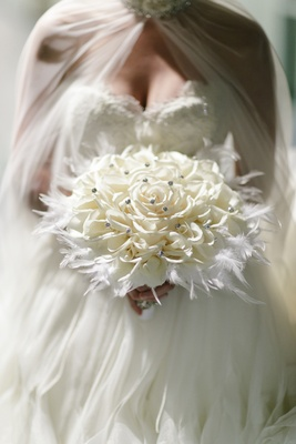 bridal glamelia bouquet dotted with crystals in bed of feathers