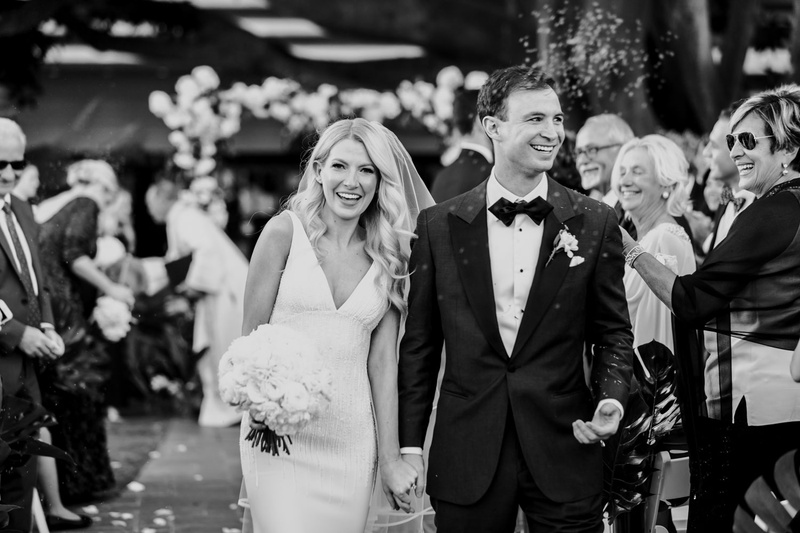 black and white photo of bride and groom walking up aisle after outdoor ceremony guests smiling