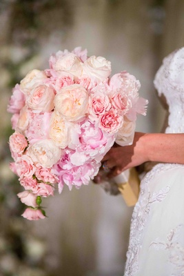 Bride holding cream roses and blush peonies
