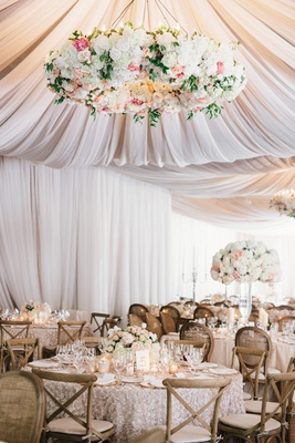 Rustic elegant tent wedding reception with large flower chandelier and texture linens high low