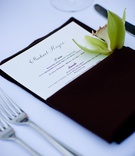Brown napkin with green orchid at wedding place setting