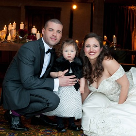 Bride and groom with young daughter in polka dots