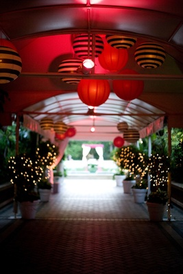 Red lighting in tunnel entryway with striped paper lanterns