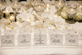wedding reception escort card table white sequin linen white orchid tea light glass orbs calligraphy
