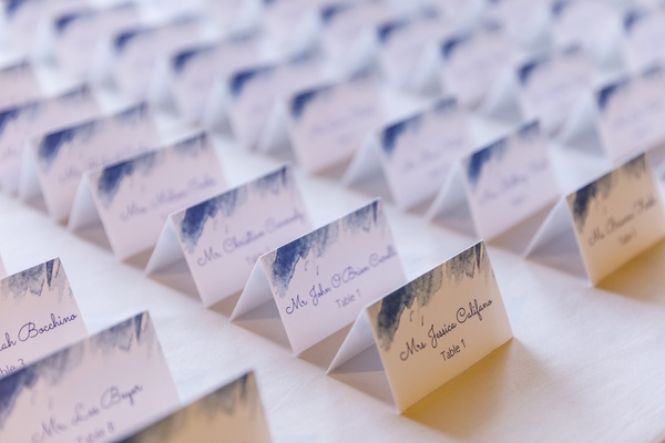 white escort cards with blue calligraphy and blue watercolor accents