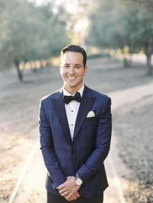 groom in blue windowpane suit jacket with navy lapels and bow tie, polka dot pocket square