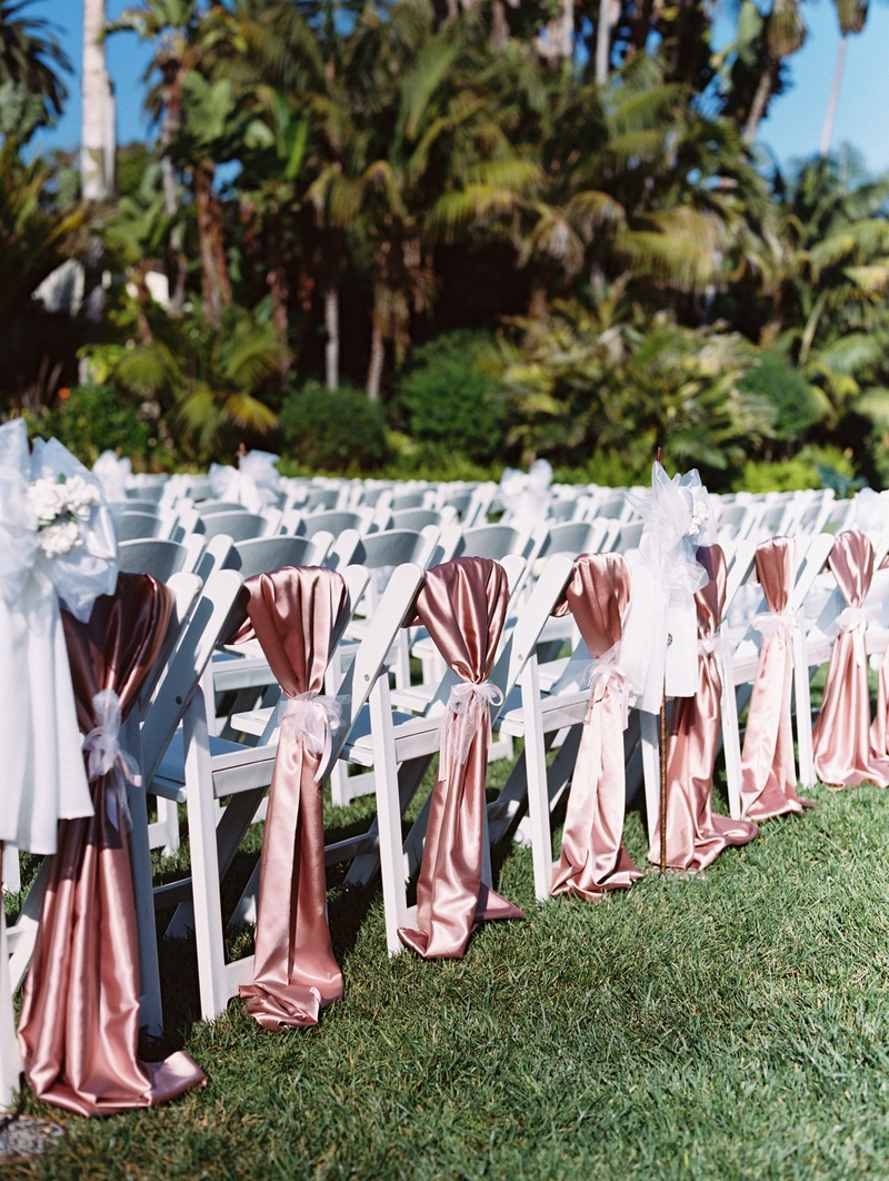 White wedding ceremony chairs on grass lawn with pink silk satin linens tied with ribbon chair cover