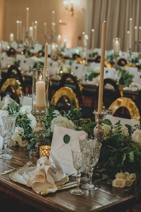 wedding reception wood table with greenery white flower tall taper candle antique style wax seal