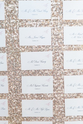 White wedding reception escort cards with pink hummingbird against a gold sequined backdrop