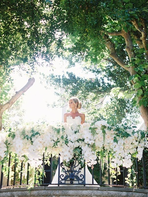 bride in white wedding gown standing on alfresco balcony covered in greenery cascading white orchids