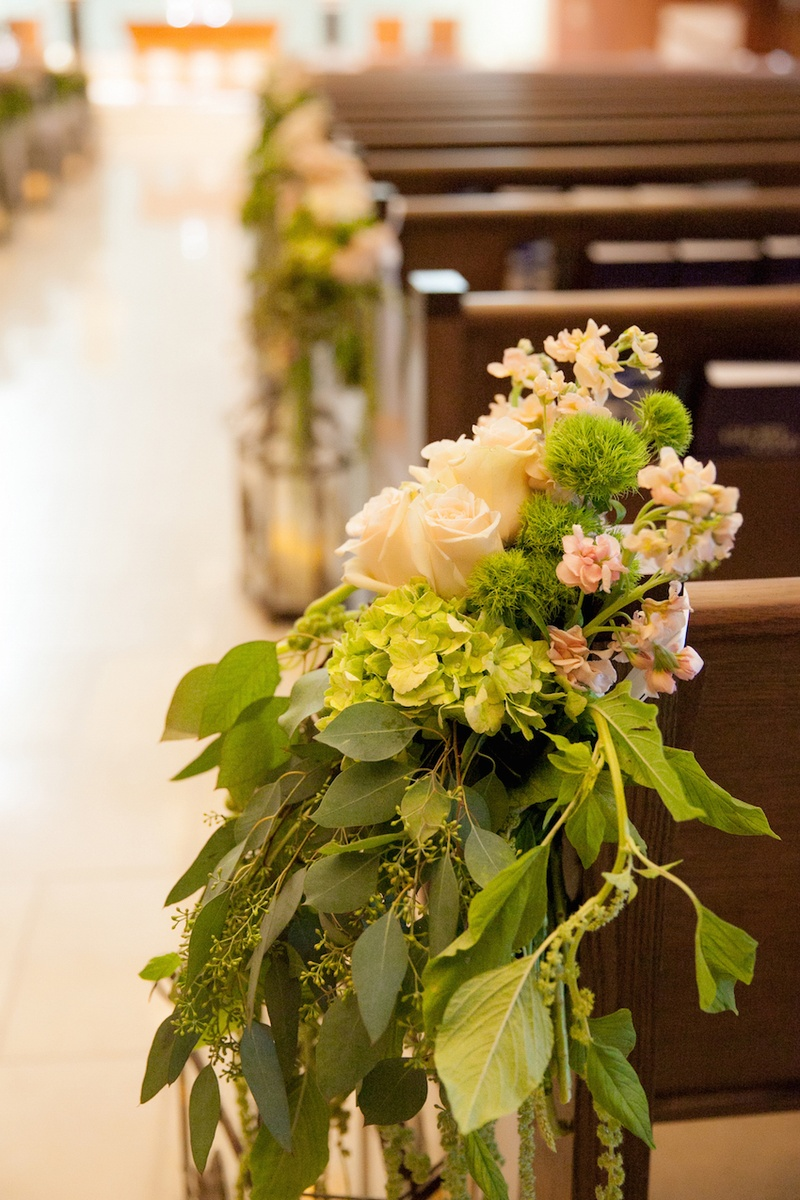 Roses and green leaves on church pews for wedding ceremony