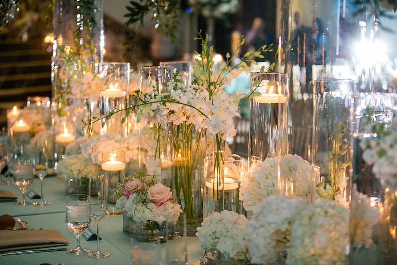 Glass vessels filled with flowers and floating candles