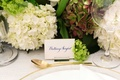 Bride's escort card with blue calligraphy new last name gold rim charger and gold spoon hydrangeas