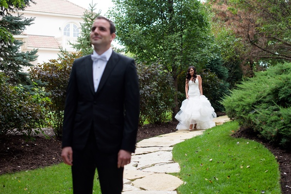 bride in monique lhuillier mermaid wedding dress walks up to groom in gibeon tolbert for first look