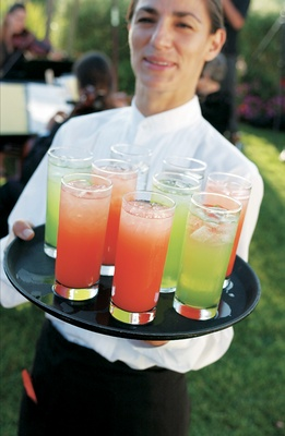Waitress holds tray of brightly colored signature cocktails