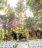 wedding ceremony stone aisle white chairs green lawn arch with fresh flowers tree backdrop