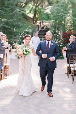 bride in pretty wedding dress groom in navy suit and burgundy tie dress shoes brick floor outdoor