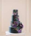 black wedding cake with purple flower details