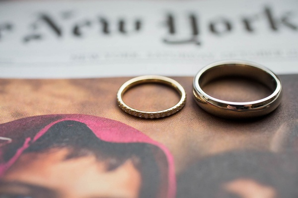 Bride's gold diamond wedding ring and groom's platinum wedding ring on New York Times