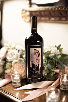 personalized wine bottle on display at wedding with engagement photo as label