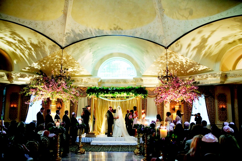 wedding ceremony with a golden post chuppah and to urns with large cherry blossom branches