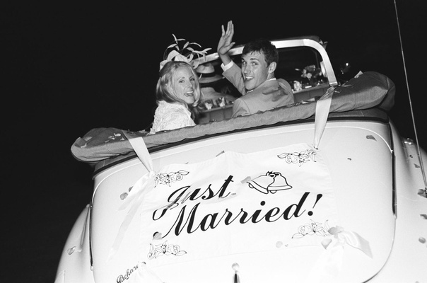 Black and white photo of couple in vintage automobile