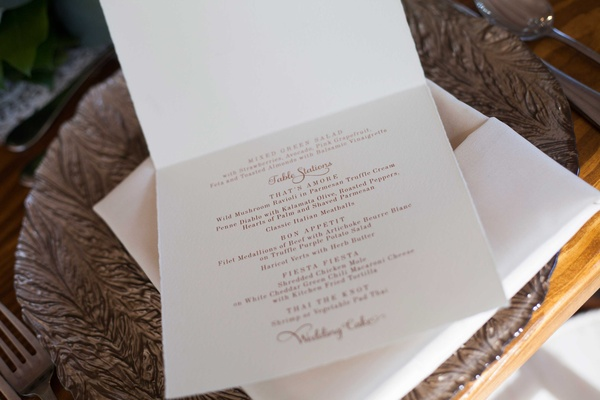 a white card with a couples reception menu in gold calligraphy