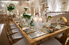 wedding reception gold mirror glass table gold chairs white cushion rose greenery centerpiece