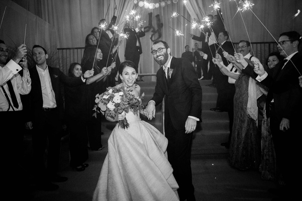 Black and white photo of bride and groom smiling during sparkler exit at wedding reception