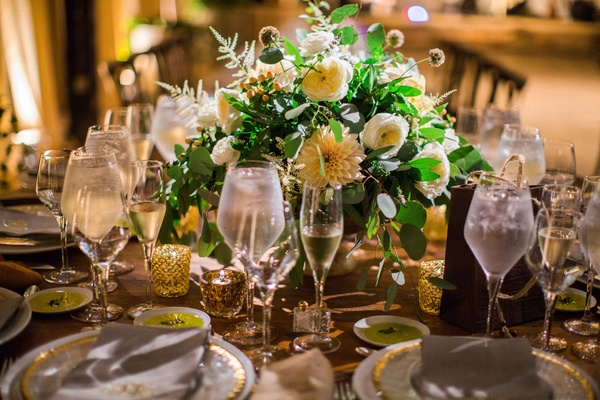Rustic wedding reception with green eucalyptus leaf ranunculus and dahlia low centerpiece wedding