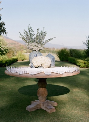 Round wood table with place cards and vases filled with flowers