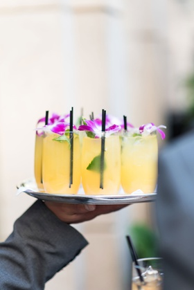 wedding cocktail hour yellow cocktail drink in glass with black straw leaves purple flower