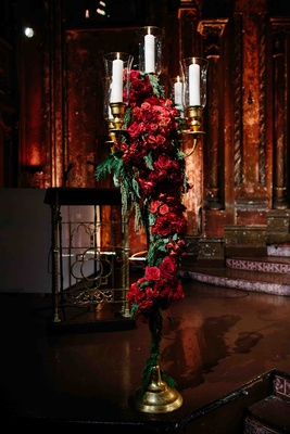 Wedding ceremony with tall golden candelabra with red roses and greenery