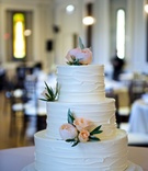 White wedding cake with stucco frosting siding, peach garden rose and green leaf decorations
