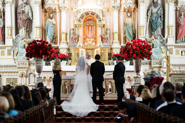 wedding ceremony catholic church red rose arrangement on both sides of altar bride in gown
