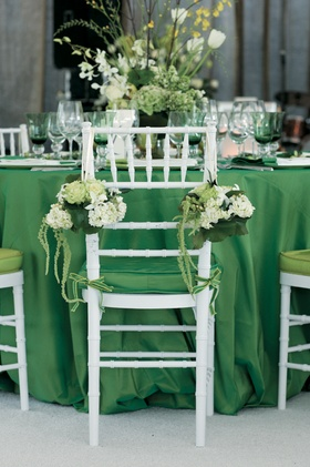 Wedding reception chair decorated with green and white flowers and greenery