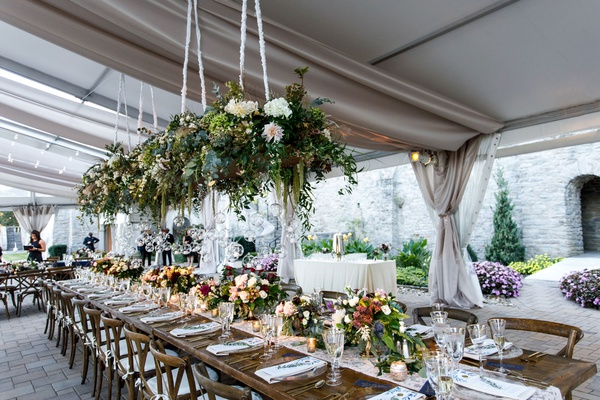 wedding reception tent head table wood farm table vineyard chairs flower chandelier overhead