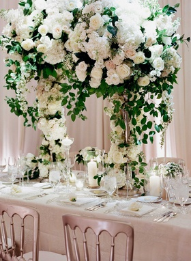 Tall wedding reception centerpiece on rectangle table silver chairs candles in glass vessels