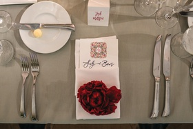 wedding place setting with red peony on napkin wrapped menu
