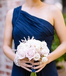 Bridesmaid in a one shoulder dark blue Monique Lhuillier dress with bouquet of pearl and blush roses