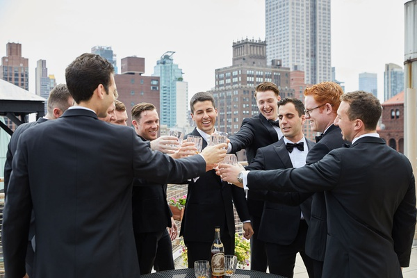 groom and groomsmen on rooftop balcony toasting rocks glasses of whiskey scotch tuxedos new york