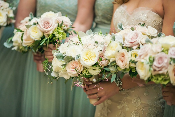 Bride and bridesmaids holding white garden rose, light pink rose, green leaves, dusty miller bouquet