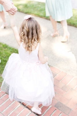 Flower girl in a sleeveless pastel pink dress and ballet slippers