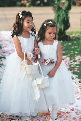 flower girls wearing white dresses with purple flowers