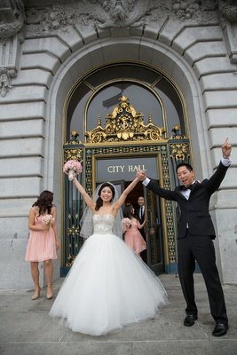 Bride in Kenneth Pool ball gown and groom in tuxedo with hands in air at San Francisco City Hall