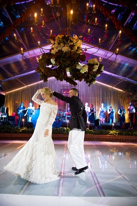 Chandelier over lighted acrylic dance floor at private home wedding with wedding band first dance