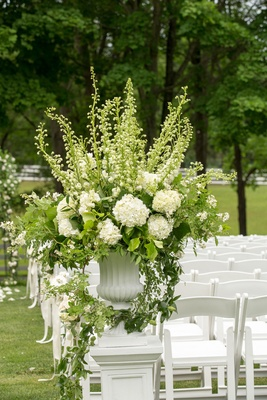 White ceremony chairs on green grass lawn white urn with greenery vines hydrangea flowers