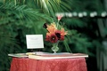 Red table with guestbook and markers at outdoor wedding